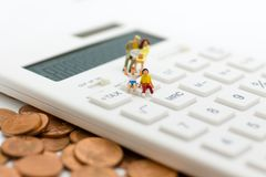 Miniature family: Family sitting on the calculator. Image use for spending to complete the every day life.  Stock Photos