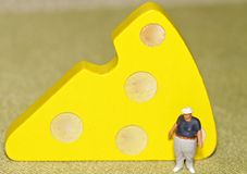 Miniature of a fat man and a slice of cheese Royalty Free Stock Photo