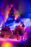 Seasons greeting with kids singing gospel with colorful christmas village blurred in the background. Holiday festive miniature. Miniature festive red background stock photo