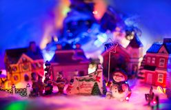 Snowman holding star of bethlehem stands next to gospel choir in front of a christmas village. Seasons greeting miniature scenery. Miniature festive red stock photo