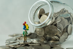 Miniature figure with balloon standing on coins, money in the ja Stock Photography