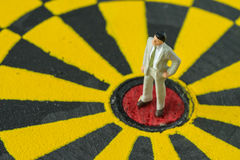 Miniature figure business man standing in the center of dartboar Royalty Free Stock Image