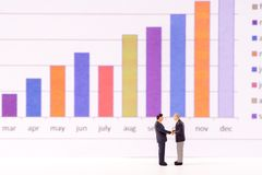 Miniature figure business people looking at bar graph chart Stock Photos