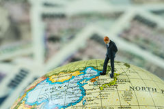 Miniature figure businessman standing and looking at north korea. Map on globe as critical war situation concept stock photos