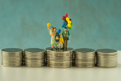 Miniature figure family with balloon standing on stack of coins Royalty Free Stock Photo