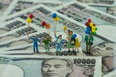 Miniature figure happy family holding balloons standing on japan. Yen banknotes as financial business or happy retirement concept Royalty Free Stock Image