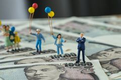 Miniature figure happy leader with his family holding balloons s. Tanding on japan yen banknotes as financial business leader concept Royalty Free Stock Photos