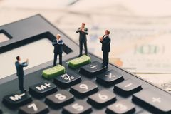 Miniature figure, leader businessman standing on calculator with stock photos