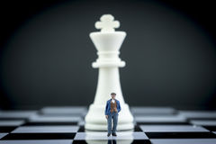 Miniature figure of a man in front of chess piece Royalty Free Stock Images