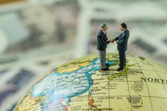 Miniature figure men handshaking standing on north korea and royalty free stock images