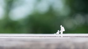 Miniature figure model of father and daughter walking together on wooden table with blur background. Closeup image of miniature figure model of father and stock photo
