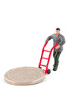 Miniature figure moving a coin over white Royalty Free Stock Photos