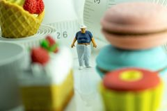 Miniature figure of an obese man and unhealthy food. Miniature figure of an obese man against measuring tape and unhealthy foods royalty free stock photography