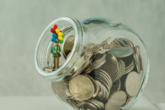 Miniature figure old man with balloon standing on coins, money i Stock Photo
