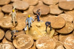 Miniature figure people working on Cryptocurrency golden bitcoin. And dollars coin money Royalty Free Stock Image