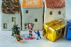 Miniature figure Santa claus giving present to happy children wi royalty free stock images