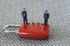 Miniature figure security guards standing on red combination pad. Lock with the background of computer numbers secret code, hacker and password protection Stock Images