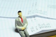 Miniature figure sitting on payroll Royalty Free Stock Images