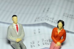 Miniature figure sitting on payroll Royalty Free Stock Photos