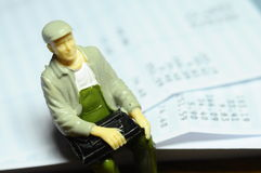 Miniature figure sitting on payroll Stock Photo