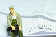Miniature figure sitting on payroll Royalty Free Stock Photography
