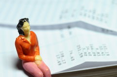 Miniature figure sitting on payroll Stock Images