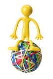 Miniature Figure Sitting on Rubberband Ball. On White Background Royalty Free Stock Image