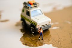 Miniature Figure : Tourist girl is walking on the map with her c stock photos