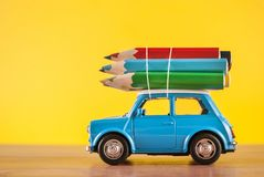 Miniature figure toy car Mini Morris carrying colored pencils on roof on yellow. Background in studio. Education and art concept royalty free stock photo