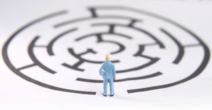 Miniature figure toy young man prepare to walk into labyrinth, face the challenges to achieve goals. Photo miniature figure toy young man prepare to walk into royalty free stock photo