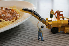 Miniature figure working on Bolognaise Stock Photography
