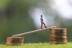 Free Miniature Figure Young Bussinesman Keep Trying To Get Higher Income Walking At Stack Of Coin At Fresh Green Grass In The Morning Stock Images - 135369964