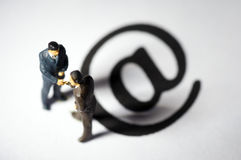 Miniature figures. Two businessman figures on '@' mark Royalty Free Stock Image