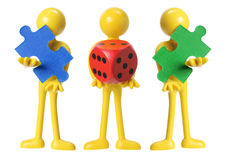 Miniature Figures with Dice and Jigsaw Puzzle Piece Royalty Free Stock Photos