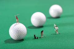 Miniature figures of golfers playing golf. Miniature figures of golfers playing a round of golf with one putting for the hole and flag an d the other teeing-off Stock Photos