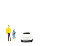 Miniature figures of people and car. On white background Royalty Free Stock Images