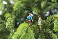 Miniature figures talking on the tree Stock Images