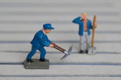 Miniature Figures of two single male workers royalty free stock photo