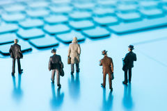 Miniature figures walking on a laptop Stock Images
