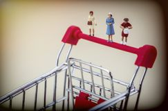 Miniature figures of women on a shopping cart Royalty Free Stock Image