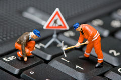 Miniature figures working on a computer keyboard. stock photography