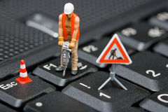 Miniature figures working on a computer keyboard. stock image