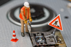 Miniature figures working on a DVD drive. Stock Images