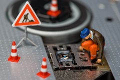 Miniature figures working on a DVD drive. Royalty Free Stock Image