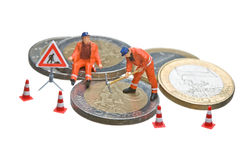 Miniature figures working on a heap of Euro coins. The objects are isolated on white, a clipping path is provided for easy extraction Royalty Free Stock Photos