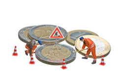 Miniature figures working on a heap of Euro coins. Royalty Free Stock Photo