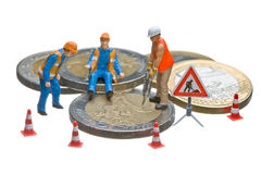 Miniature figures working on a heap of Euro coins. Royalty Free Stock Image