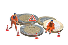 Miniature figures working on a heap of Euro coins. Stock Photos