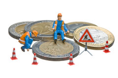 Miniature figures working on a heap of Euro coins. Stock Photo