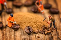 Figures working on coffee. Miniature figures working on instant coffee macro photography on wood table royalty free stock photos